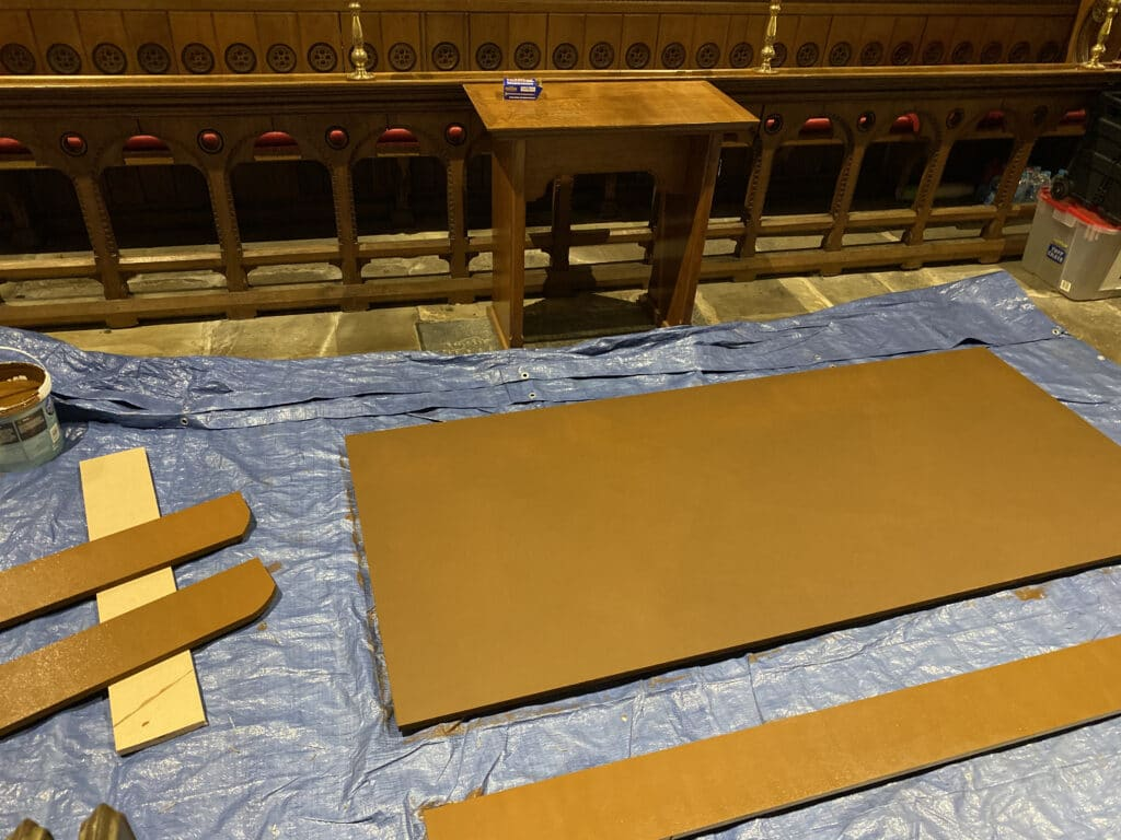Parts of wood lying on a tarpaulin on the church floor, waiting for woodstain to dry