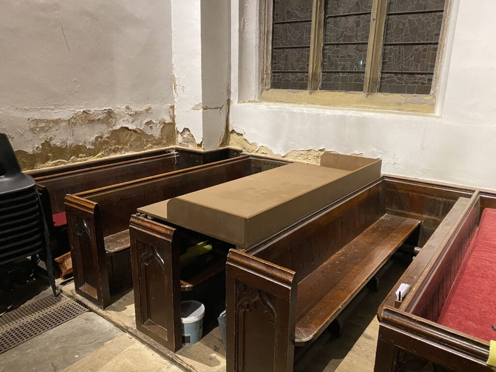 A finished wooden desk with raised back and sides, straddling the backs of two pews