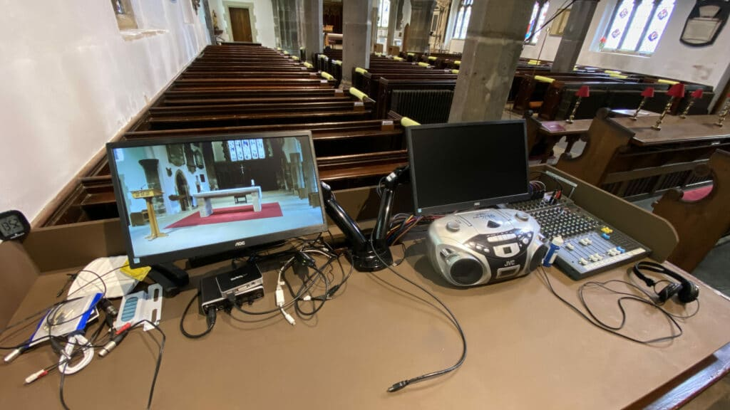 A photograph of the technology desk at the back of the church building. It shows two monitors mounted on adjustable arms, a CD player and a sound mixing desk with a pair of headphones.