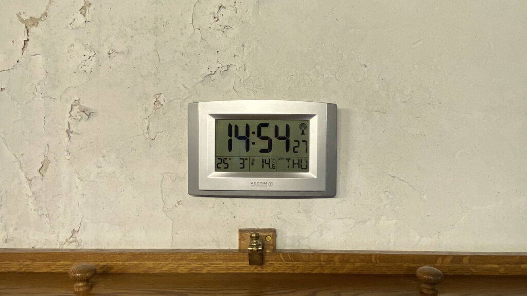 A digital clock mounted to a wall, displaying the date, day of the week, time and temperature.